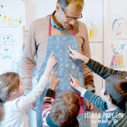 Alumnos señalando al delantal del profesor azul y rojo personalizado con dibujos de línea y los nombres de los niños de la clase con su caligrafía en blanco