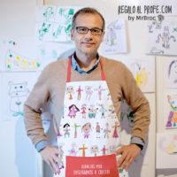 Profesor con delantal blanco y rojo personalizado con dibujos coloreados de los niños de la clase