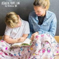 Profe y alumno con manta personalizada con los dibujos coloreados y los nombres de los niños de la clase
