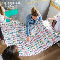 Profe recibe de alumnos manta personalizada con los dibujos coloreados y los nombres de los niños de la clase