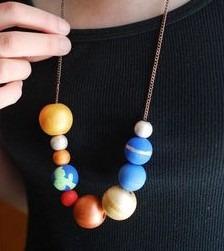 Foto collar hecho por niños con bolas que representan planetas